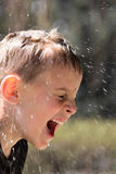Soaking wet young boy laughing hysterically Royalty Free Stock Photos