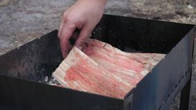 Soaking wood logs in the grill before BBQ stock footage