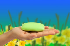 Soap bar in hand on abstract background. Royalty Free Stock Images