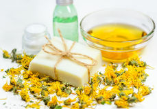 Soap bar. Natural soap bar on dry yellow flowers at olive oil and bottles background. Spa treatment and skin care Stock Images