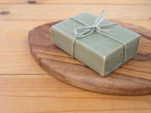 Soap bar tied with jute rope on the olive tree textured board Royalty Free Stock Photo