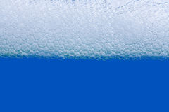 Soap bath bubbles macro view. Laundry detergent, suds textured pattern. White soapsuds on blue background, copy text Stock Photography