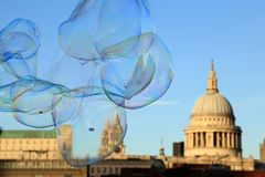 Soap bubble on blue sky with blurred scene of St Paul`s Cathedral, London, UK.  stock image