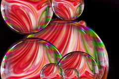 Soap bubble with Colorful liquid paints mixed together creating pattern.rainbow colors on black background stock photos