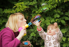 Soap bubble family fun. Mother and daughter having fun with soap bubbles Royalty Free Stock Photography