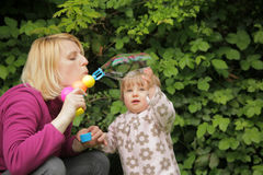 Soap bubble family fun. Mother and daughter having fun with soap bubbles Stock Photos