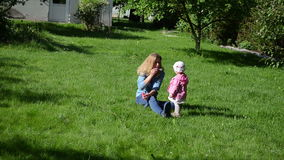 Soap bubble family. Mother and daughter have fun spending a summer afternoon in the garden sitting in the meadow blowing soap bubbles stock footage