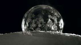 Soap bubble freezing on black bagground. Fast Freezing Soap bubble. Ice ball with flying snowflakes flowers on snow and black background in cold winter. For stock footage