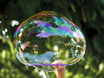 Soap bubble. Hand of a child holding a hoop with a big soap bubble royalty free stock images