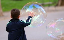 Soap Bubble. Kid playing with big soap bubble Royalty Free Stock Images