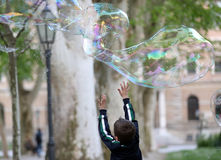 Soap Bubble. Kid playing with big soap bubble Royalty Free Stock Image