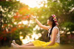 Soap bubble rain. Asian teenager girl in the park under soap bubble rain Stock Photo