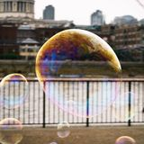 Soap bubble with the reflection of buildings in London with view on the river Thames royalty free stock image
