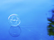 Soap bubble sliding on water Royalty Free Stock Photo