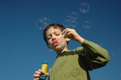 Soap bubbles. Boy blowing soap bubbles Stock Photos