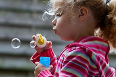 Soap bubbles. A little girl blowing soap bubbles Stock Image