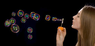 Soap-bubbles. The teenage girl is blowing soap-bubbles on the black background Stock Images