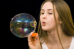 Soap-bubbles. The teenage girl is blowing soap-bubbles on the black background Stock Image