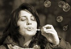 Soap bubbles. Young woman makes soap bubbles in park Stock Image
