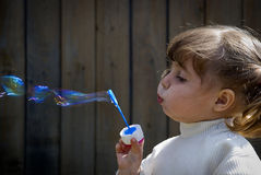 Soap bubbles. Small pretty girl blowing colourful soap bubbles Stock Images