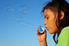 Soap bubbles. Little girl blowing soap bubbles, close up Royalty Free Stock Photo