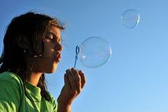 Soap bubbles. Little girl blowing soap bubbles, close up stock photo
