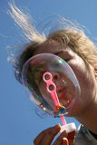 Soap bubbles. Girl blowing soap bubbles on sky background Royalty Free Stock Photography