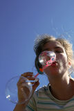 Soap bubbles. Girl blowing soap bubbles on sky background Stock Image