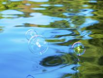 Soap bubbles above water Stock Image