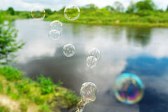 Soap bubbles against the beautiful lake. Soap bubbles fly against a beautiful spring landscape Royalty Free Stock Photography