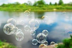 Soap bubbles against the beautiful lake. Soap bubbles fly against a beautiful spring landscape Stock Photos