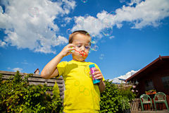 Soap bubbles. Cute kid blowing soap bubbles Stock Photography