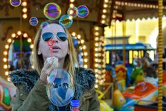 Soap Bubbles. A female blonde model blowing soap bubbles at a merry-go-round Royalty Free Stock Photo