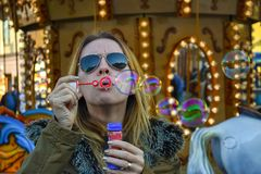 Soap Bubbles. A female blonde model blowing soap bubbles at a merry-go-round Stock Image