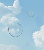 Soap bubbles. Floating soap bubbles against clear sunlit blue sky and clouds Stock Photo