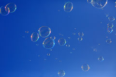Soap bubbles floating in a blue sky Stock Photos