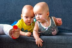 Soap bubbles in the foreground. In the background are twins, a boy and a girl of 7 months. Maternity. Soap bubbles in the foreground. In the background are royalty free stock image