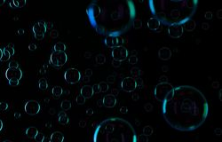 Soap bubbles isolated on black background. Rainbow soap bubble. Bright green and orande colors. 3d rendering royalty free illustration