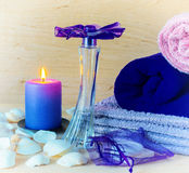 Soap, candle, perfume. Still life. colored towels, soap, candle and perfume on a background of a wooden table Stock Image