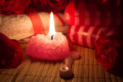Soap, candle and roses. Soap, candle and a rose on a bamboo the mat Royalty Free Stock Photo