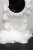 Soap coming out from broken washing machine stock photography