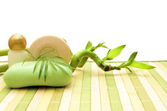 Soap, cosmetics and bamboo. Aroma soap, cosmetics and bamboo on striped mat Royalty Free Stock Image