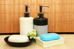 Soap dispensers and bars. On bamboo Royalty Free Stock Photos