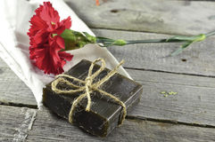 Soap with flower. Vintage still life with red flower and black soap on wooden background Stock Photos