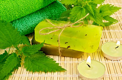 Soap green homemade with nettle and candles Royalty Free Stock Photo