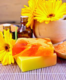 Soap homemade and oil with calendula on bamboo Royalty Free Stock Images