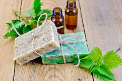 Soap homemade and oil with nettle on board Royalty Free Stock Photos
