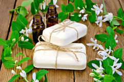 Soap and oil white with  flowers of honeysuckle on board Royalty Free Stock Photography