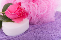 Soap with a pink rose on top of a purple towel, with a pink shower puff Royalty Free Stock Photo