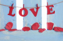 Soap rose petals and the word love. Red rose petals made of soap, spread on a blue wooden fence and the word love spelled with red paper letters and tied to a Royalty Free Stock Image